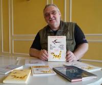 """Uwe Jordan mit seinem erklärten Lieblingsbuch  """"Der gestreifte Kater und die Schwalbe Sinhá"""" von Jorge Amado."""